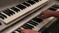 Ein Musiker spielt ein Klavier und Keyboard