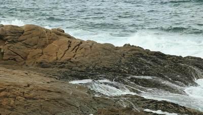Ocean waves hitting beach rocks.