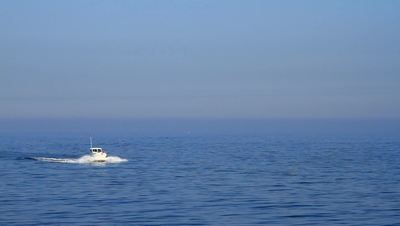 A blue shot with a boat sailing on the sea