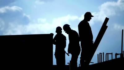 Silhouette of construction workers and a blue sky stock video