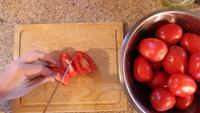 Top-down-view-of-man-cutting-tomatoes-on-wood-cutting-board