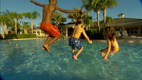 Kids jump into resort swimming pool