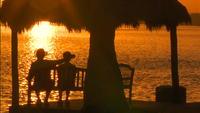 Senior par njuter av solnedgången