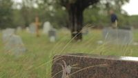 A man walks in the background of a cemetery