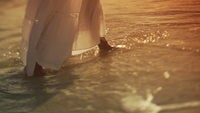 A couples feet walking in the water at the beach