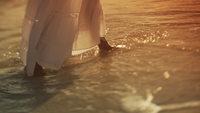 Un par de pies caminando en el agua en la playa