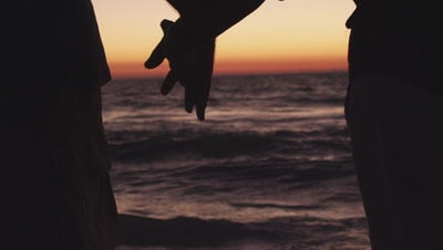 Couple holds hands on beach at sunset