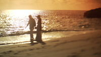 Couple walk along sandy beach at sunset