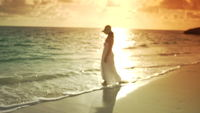 Mujer en vestido blanco caminando en la playa