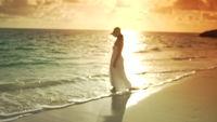 Frau im weißen Kleid zu Fuß am Strand