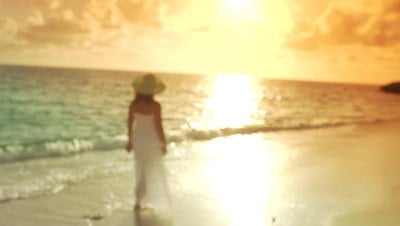 Woman in white dress walks along the shore
