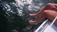 Woman's feet hanging off sailboat