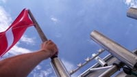 Hand puts in dive flag on boat