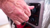 Hand starts outboard motor on boat