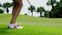 Kvinna golfer chip till grön