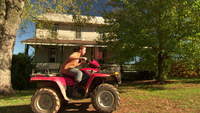 Boy riding ATV into farmland