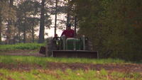 Man riding tractor around farm