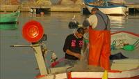 Fishermen fix casting net in boat