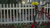 A bike on a white picket fence