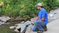 Man-fishing-off-bridge-in-creek-reeling-in-fishing-pole
