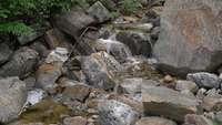 Water stromen tussen rotsen 4k