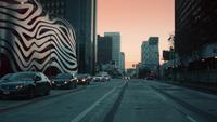 Tracking shot of streets and Petersen Automotive Museum at Los Angeles in 4K car driver view