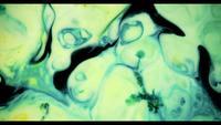 Pintura amarilla y azul que se mezcla para crear formas redondeadas aleatorias verdes en la superficie blanca
