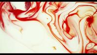 Red paint moving on white paint surface creating organic and dynamic textures in 4K