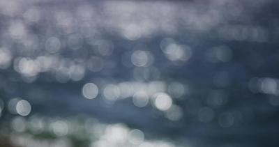 Bokeh clip of sunlight reflecting on the sea.