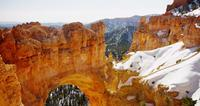 Horizontal panning shot of red stone arch and snowy valley in 4K