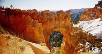 Langzame verticale panning shot van stenen boog en besneeuwde vallei in 4K