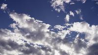 Tijdspanne van altocumuluswolken die zich langzaam op heldere blauwe hemel en zonlichtstralen in 4K bewegen