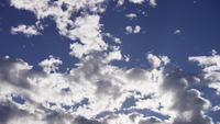 Time lapse of altocumulus clouds moving slowly on bright blue sky from right in 4K