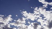 Time lapse of clear and bright altocumulus clouds moving on blue sky with sunlight rays in 4K