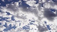 Tidsförlust av klara och gråa altocumulus moln som rör sig på blå himmel med solljusfläckar i 4K
