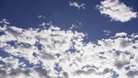 Time lapse of altocumulus clouds with sunlight flares in the bottom of the scene in 4K