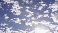Tijdspanne van groep altocumuluswolken die zich op blauwe hemel met zonlicht flakkeren in de bodem in 4K bewegen
