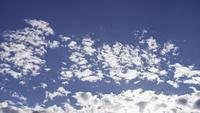 Time lapse of several groups of altocumulus clouds moving on blue sky with sunlight flares in 4K