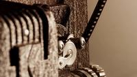 Extreme close-up van 8 mm-filmprojector en detail van het tandwielmechanisme met film en rollen in actie in 4K