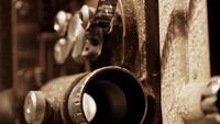 Extreme close-up van een 8mm-filmprojector waarbij de lens met een knipperend licht en flim in 4K flitst