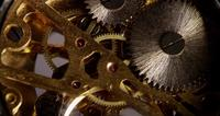 Extreme close up of pocket watch machinery with golden gears in 4K