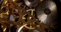 Extreme close up of pocket watch machinery with small gears spinning in 4K