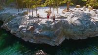 Drone shot of people cliff jumping into a swimming hole | Free Stock Footage