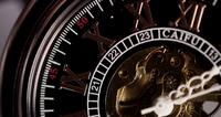 Extreme close up of pocket watch with exposed machinery working twenty minutes in 4K time lapse