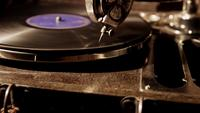 Vertical panning shot of antique record player with old vinyl disc spinning in 4K