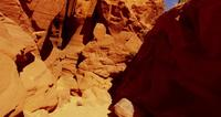 Slow traveling shot inside a geological formation showing bright orange walls and rocks in 4K