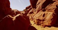 Traveling shot inside a natural geological formation showing orange walls and rocks in 4K