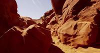 Traveling shot inside a natural geological formation showing orange walls and rocks in 4K