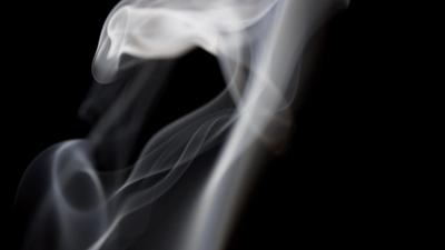 Blurred smoke in background and focused smoke in foreground dancing in darkness in 4K