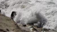 Zusammenstoßende Wellen auf einem felsigen Strand